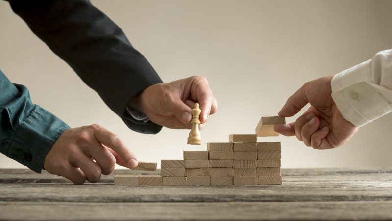 Business teamwork concept with a businessman moving a chess piec